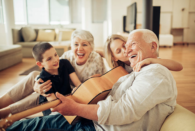 white-hair man holding a guitar, white hair woman laughing, dark-haired boy, blonde girl